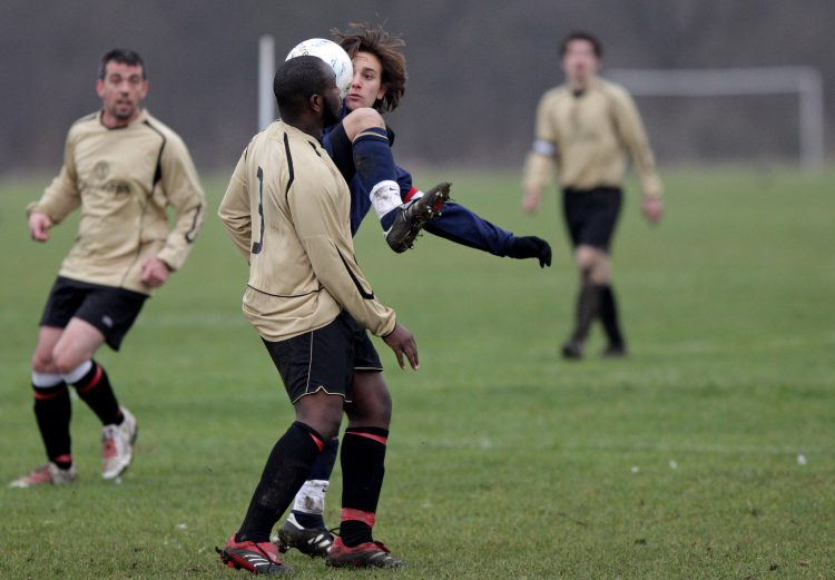 LONDON, ENGLAND - JANUARY 24: Two Sunday League footballers challenge for the ball during a match on the Hackney Marshes