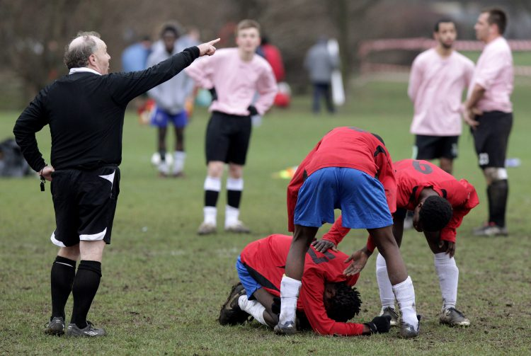 LONDON, ENGLAND - JANUARY 24: Sunday League footballers console an injured teammate during a match on the Hackney Marshes