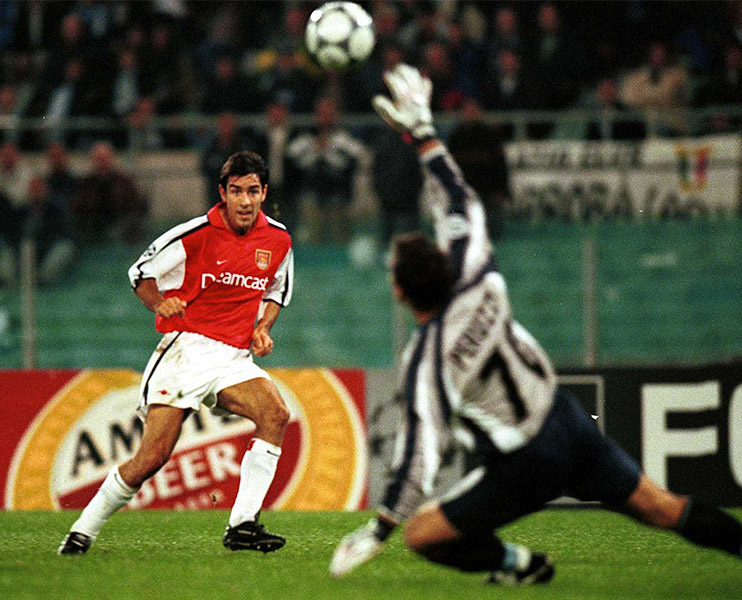 Robert Pires chips Lazio keeper Angelo Peruzzi in the Champions League
