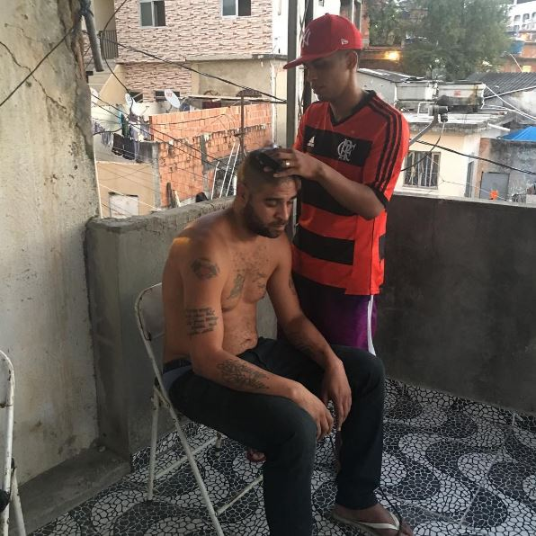 Adriano getting his haircut in a Brazilian favela