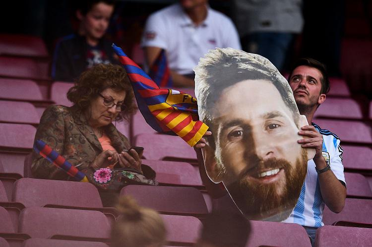 A fan holds an oversized Messi mask