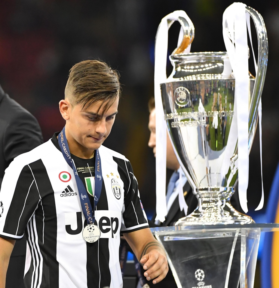 Paulo Dybala walks past the Champions League trophy after loss to Real Madrid