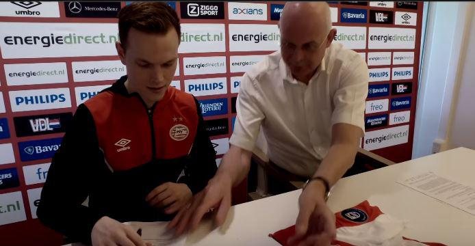 Kok is seen signing a contract in the trailer
