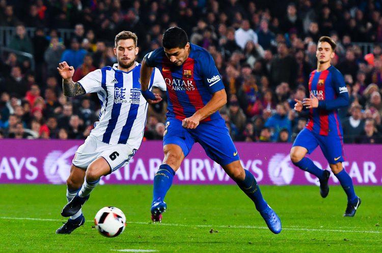 Inigo Martinez (left) tries to put a reducer on Luis Suarez (right)