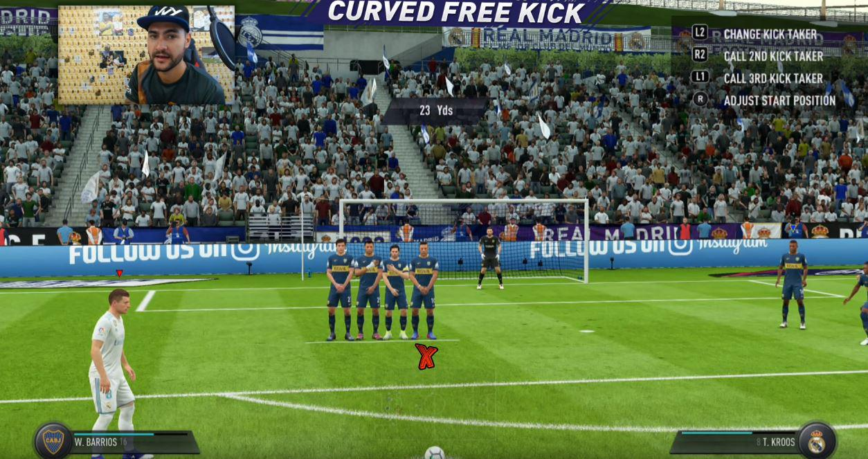 Aim for the first man in the wall – and then curve the ball over his head to the top right hand corner of the goal (left side on the screen)