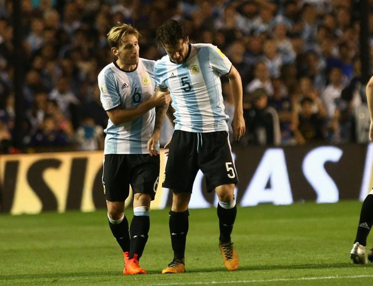 Gago is helped to his feet by Lucas Biglia