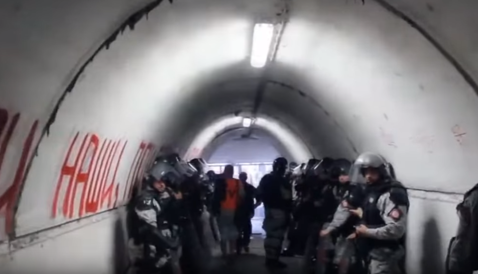 Armed guards line the walls on either side