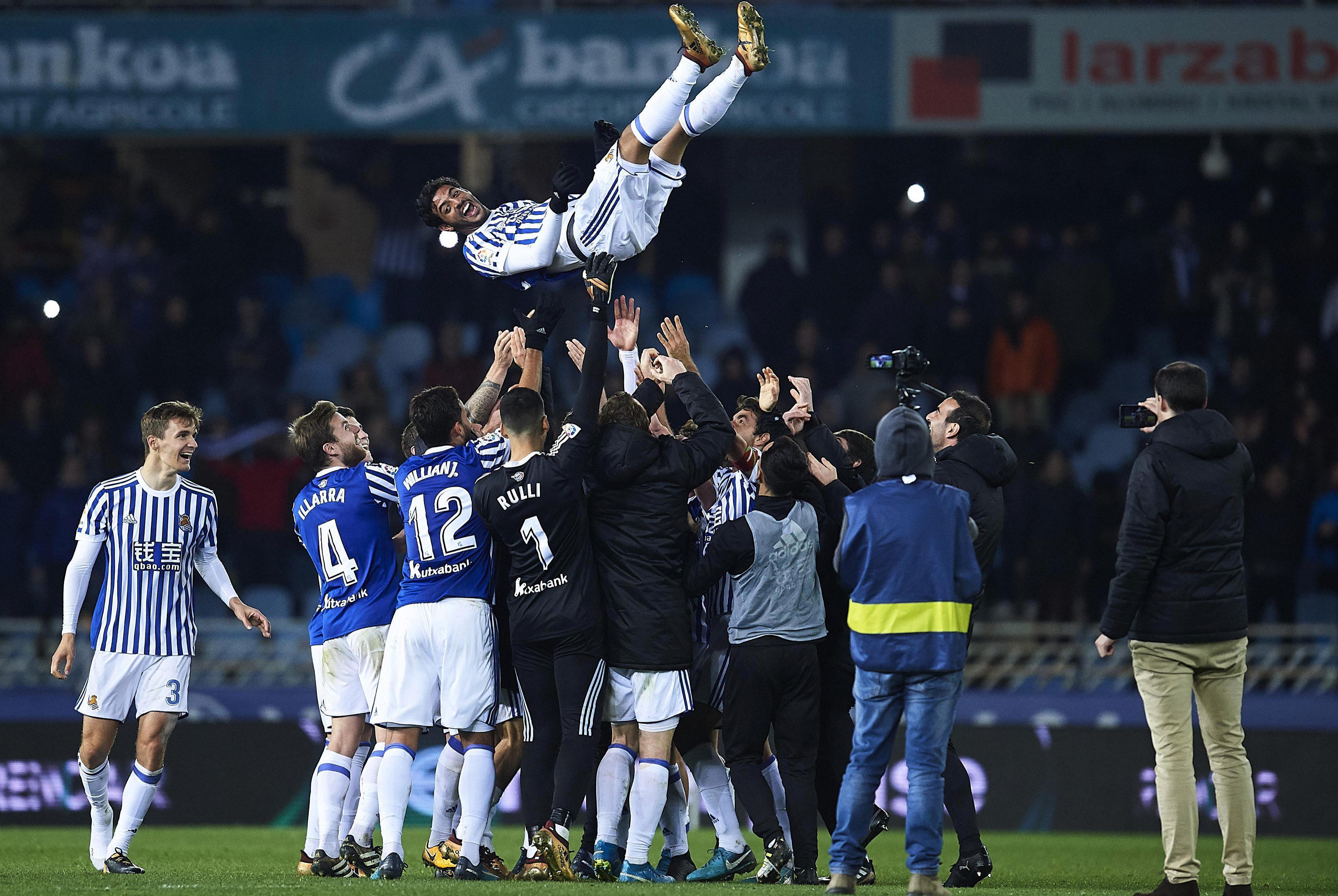 His team-mates throw him high in the air