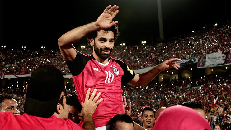 Held aloft after his winner against Congo
