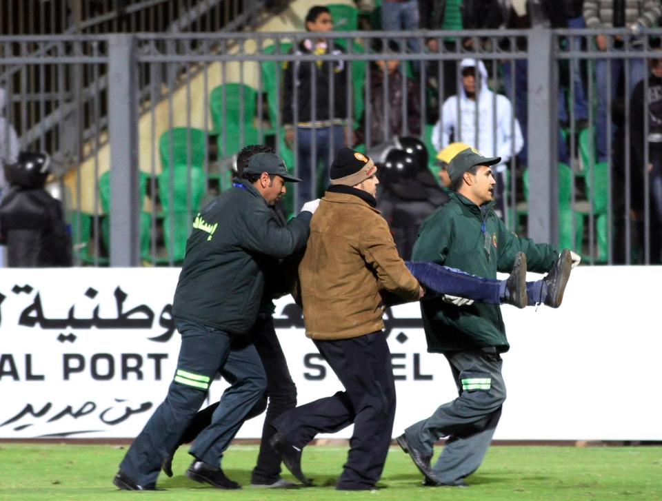 An injured fan is carried away on a stretcher