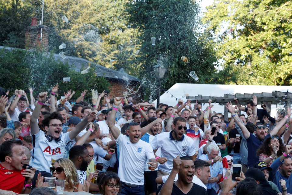 Supporters at Ye Olde Fighting Cock in St Albans throw their pints into the air after England take the lead