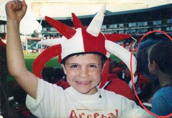 A young Samuel forcing a smile as his brother wears the kit behind him